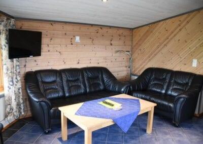 Stue med sofaer, bord og TV.