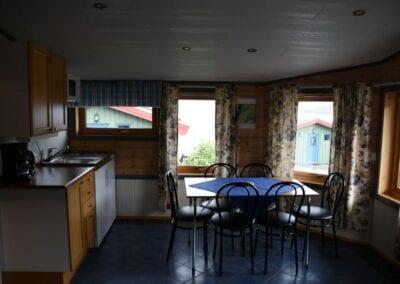 Kjøkken med spisebord, stoler, oppvaskbenk, kaffetrakter og mikrobølgeovn.