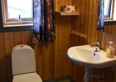 Bad med toalett, vask, speil og vindu.