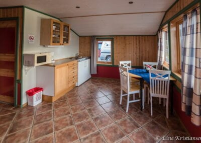 Kitchen with dining table, chairs, sink, coffee maker and microwave.