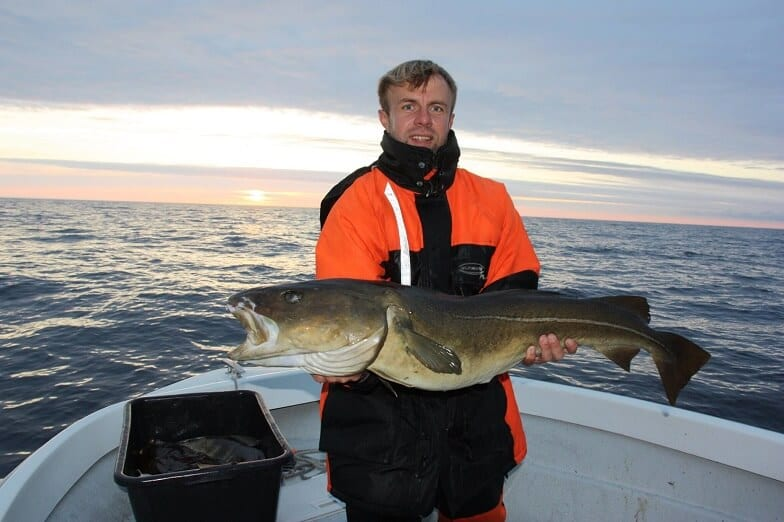 Ein Fischer, der einen Fisch hält.