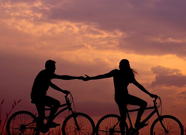 To personer som sykler og holder hender.